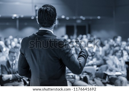 Speaker giving a talk on corporate business conference. Unrecognizable people in audience at conference hall. Business and Entrepreneurship event. Royalty-Free Stock Photo #1176641692