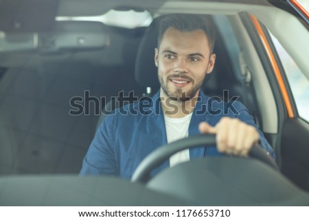 Young man smiling, happily sitting in new automobile at car showroom. Handsome male client, wearing in blue jacket and white t-shirt, holding one hand at wheel and looking at side in brand-new car. #1176653710