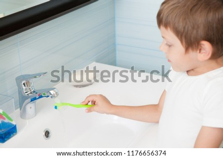 healthy little caucasian kid with toothbrush in hand in morning hygiene bathroom #1176656374