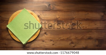 pizza or bread cutting board and napkin cloth at wooden table, top view #1176679048