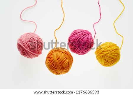 Colorful woolen balls over white background. Balls of wool partially unrolled.  #1176686593