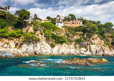 Rocky coastline in mediterranean in Lloret de Mar, Costa Brava, Spain with village houses on hills and mountain. Beautiful view on house on rocks on sea shore. Life in Mediterranean on summer day #1176703864