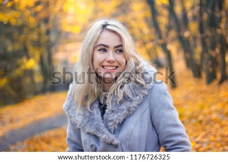 Portrait of a beautiful girl in an autumn park. #1176726325