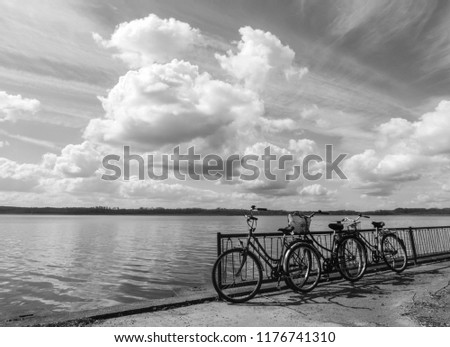 peaceful black and white vintage photo of 3 bicycles by the lake under the vast cloudy sky
