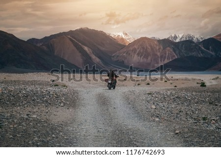 Tourist riding an adventure motorcycle on tuff and bumpy road on rock mountain in sunset lightning to explore the world, with copy space  #1176742693