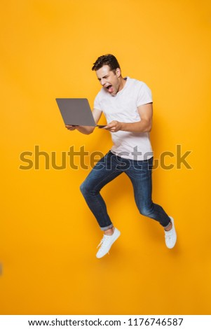 Photo of excited young man jumping isolated over yellow wall background using laptop computer. #1176746587