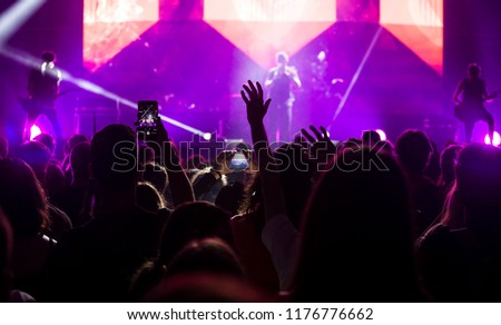 Crowd at concert - Cheering crowd in bright colorful stage lights #1176776662