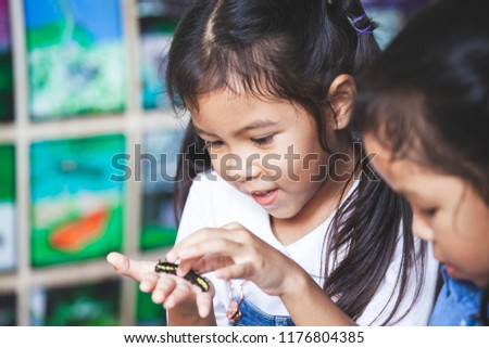 Cute asian child girl holding and playing with black caterpillar with curious and fun. Black caterpillar crawling on her hand. #1176804385
