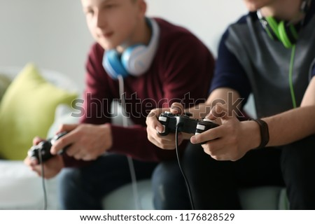 Teenagers playing video games at home #1176828529