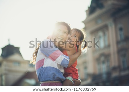 It's fun when we're together. Mother having fun with her little daughter on city street. Copy space. Close up.  #1176832969