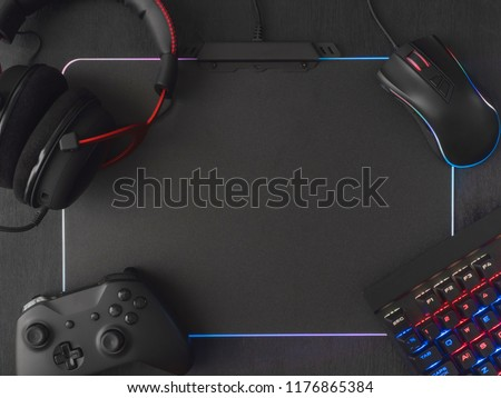 e-sport concept, top view a gaming gear, mouse, keyboard, joystick, headset, mobile joystick, in ear headphone and mouse pad on black table background. #1176865384
