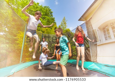 Happy children jumping on the outdoor trampoline #1176905533