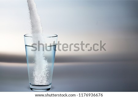 Pouring powder on water glass on  background