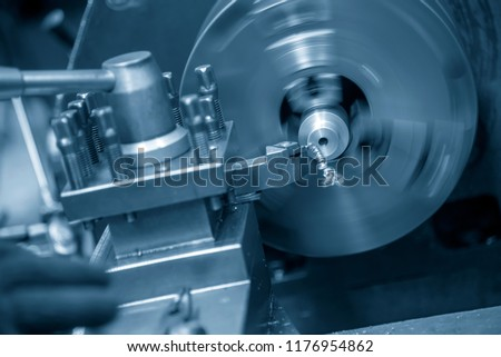 The  operation of lathe machine cutting the steel shaft in the light blue scene. #1176954862