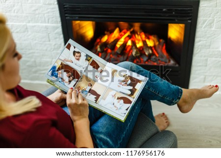 High angle view of young girl looking through photo album at home