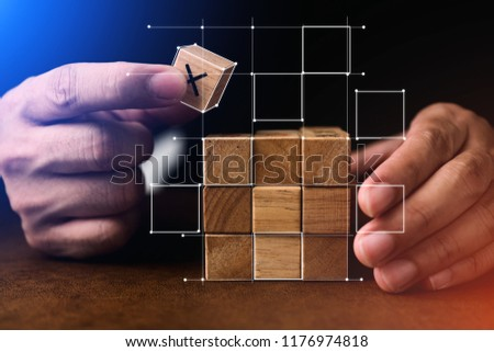 business man try to build wood block on wooden table and blur background business organization startup concept #1176974818