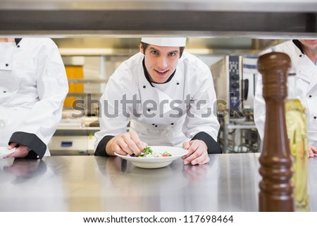 Chef garnishing his salad and smiling in the kitchen #117698464