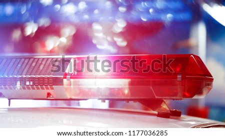 Police patrol car of the specialized unity in the night time. Red and blue flashes on the car of the emergency vehicle. Police lights during traffic surveillance on the city road. Flash lights.