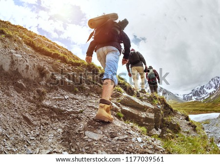 Group of three tourists walking uphill by trek in mountains Royalty-Free Stock Photo #1177039561
