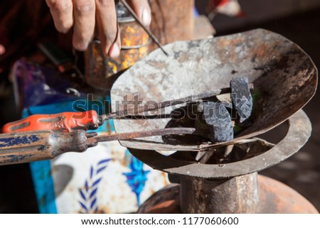 Moroccan blacksmith working with chisel and hammer in Marrakech Morocco #1177060600