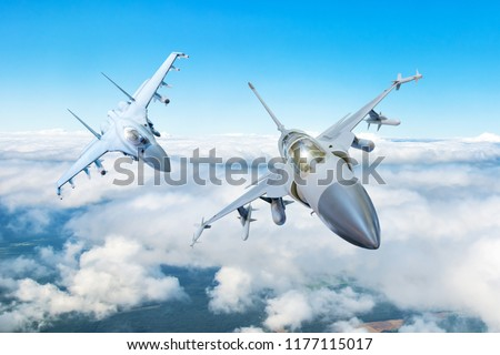 Pair of combat fighter jet on a military mission with weapons - rockets, bombs, weapons on wings flies high in the sky above the clouds #1177115017