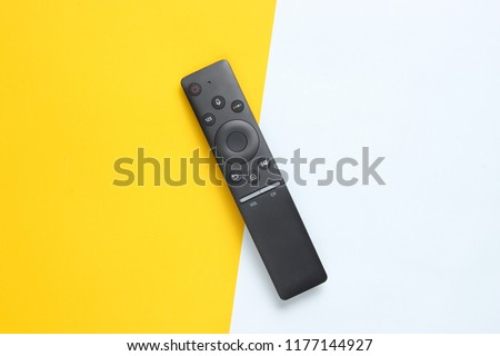 A modern TV remote control on pastel background. Top view, minimalism #1177144927