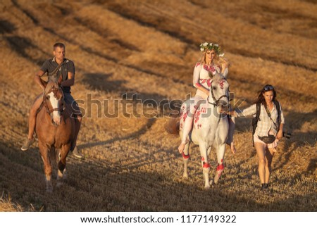 MINSK, REPUBLIC OF BELARUS - SEPTEMBER 3, 2018: Field shooting of a girl and a horse in body painting. The film crew and make-up artist go to the shooting site. #1177149322
