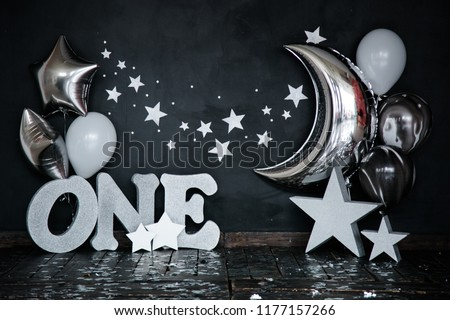Smashed first birthday white cake with stars and one candle for little baby boy and decorations. Black background. Big silver letters ONE, silver stars and different balloons.