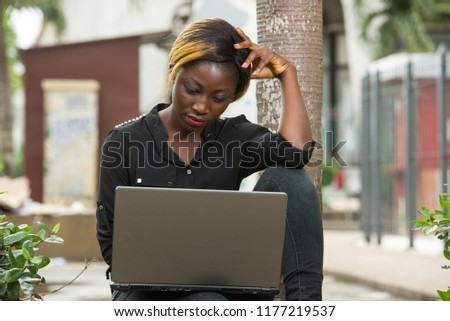 young woman sitting outside and looking pensive on a laptop. #1177219537