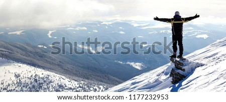 Silhouette of alone tourist standing on snowy mountain top in winner pose with raised hands enjoying view and achievement on bright sunny winter day. Adventure, outdoors activities, healthy lifestyle. #1177232953