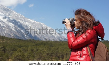 girl photographer take picture and focus on the beautiful snow mountain landscapes in China Yunnan province
