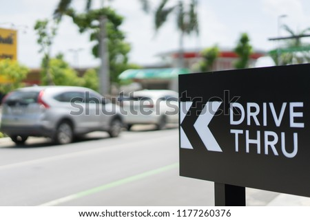 Drive thru sign with blur Car on background #1177260376