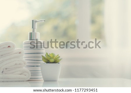 Ceramic soap, shampoo bottles and white cotton towels on white counter table inside a bright bathroom background. #1177293451