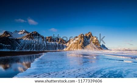 Ocean waves roll up on black beach in front of Vestrahorn mounta #1177339606