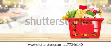 Food and groceries in shopping basket on wood table with blurred suppermarket in background, panoramic banner with copy space Royalty-Free Stock Photo #1177346140