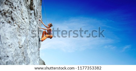 side view of young slim woman rock climber in bright orange pants climbing on the cliff. a woman climbs on a vertical rock wall on the blue sky background #1177353382