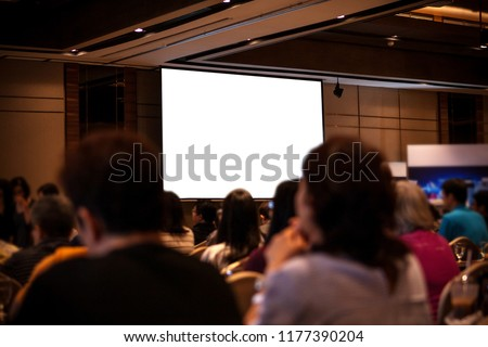 Blurred of photo rear view of Audience in the conference hall or seminar meeting with blank screen display on white board. #1177390204