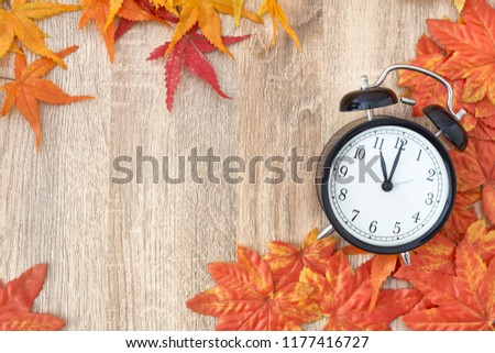 Old clock on autumn leaves on wooden table on natural background, day noon light Blank Space for text #1177416727