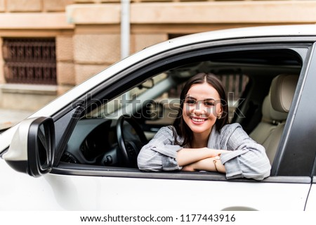 Closeup portrait attractive woman buyer sitting in her new car excited ready for trip isolated outside dealer dealership lot office. Personal transportation auto purchase concept Royalty-Free Stock Photo #1177443916