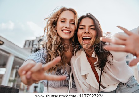 Lovable caucasian girls expressing positive emotions to camera. Outdoor photo of refined sisters posing on sky background. #1177527226