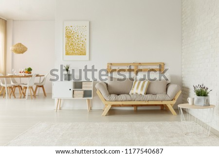 Gold poster above white cabinet next to beige wooden settee in loft interior with table. Real photo #1177540687