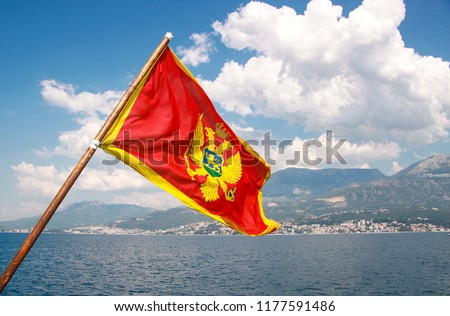 Montenegro flag at Kotor bay. Flag of Montenegro on a background of mountains and Adriatic sea. Space for text. #1177591486