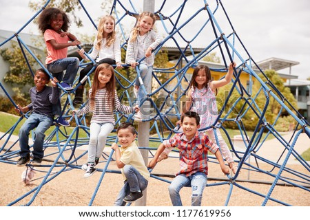 Elementary school kids climbing in the school playground Royalty-Free Stock Photo #1177619956