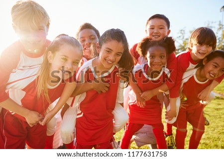 Kids in elementary school sports team piggybacking outdoors Royalty-Free Stock Photo #1177631758