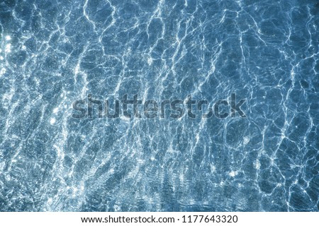 Blue water and pouring mica through a layer of glitter water. A backdrop of the sea and ocean depth  #1177643320