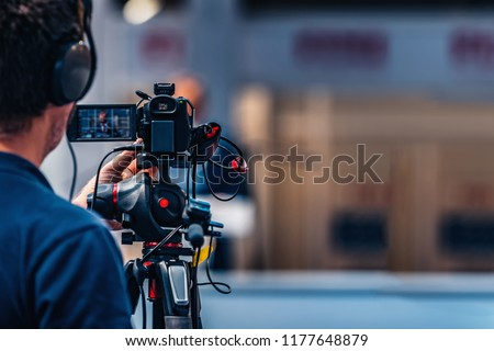 Cameraman recording male speaker wearing suit at media press conference. Live streaming concept. #1177648879