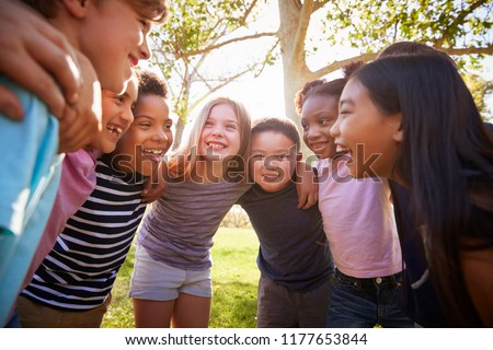 Group of schoolchildren embrace standing in a circle #1177653844