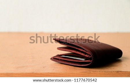 Brown leather wallet put on wooden table top Royalty-Free Stock Photo #1177670542