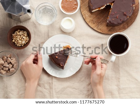 Women's hands holding a plate with piece of Peanut Butter Chocolate Caramel Cheesecake Pie. Top view of a Coffee Break concept with cup of coffee on dining table with linen tablecloth #1177675270