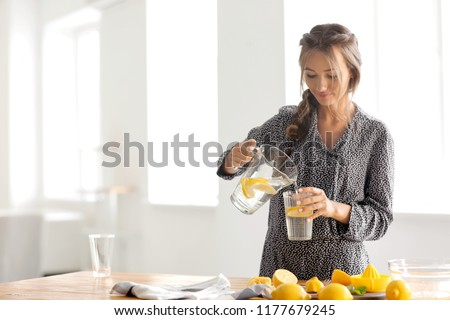 Young woman pouring fresh lemonade from jug into glass at home #1177679245